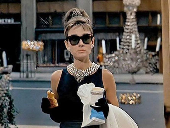 A icônica cena de Holly Golightly, interpretada por  Audrey Hepburn, tomando café em frente à joalheria Tiffany