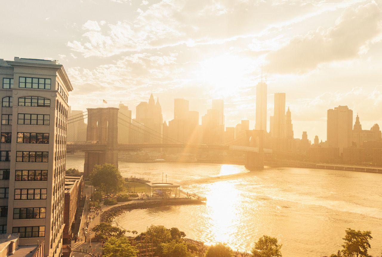 sunset over the Brooklyn Bridge and New York City skyline.