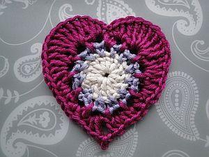 A crochet heart appliqué with a classic shape and a pretty center