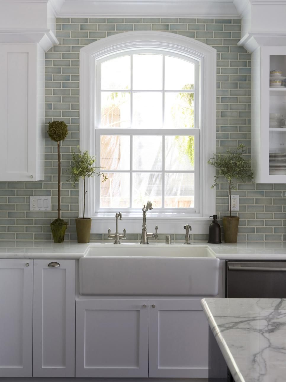 A ceramic farmhouse sink with a brushed nickel
