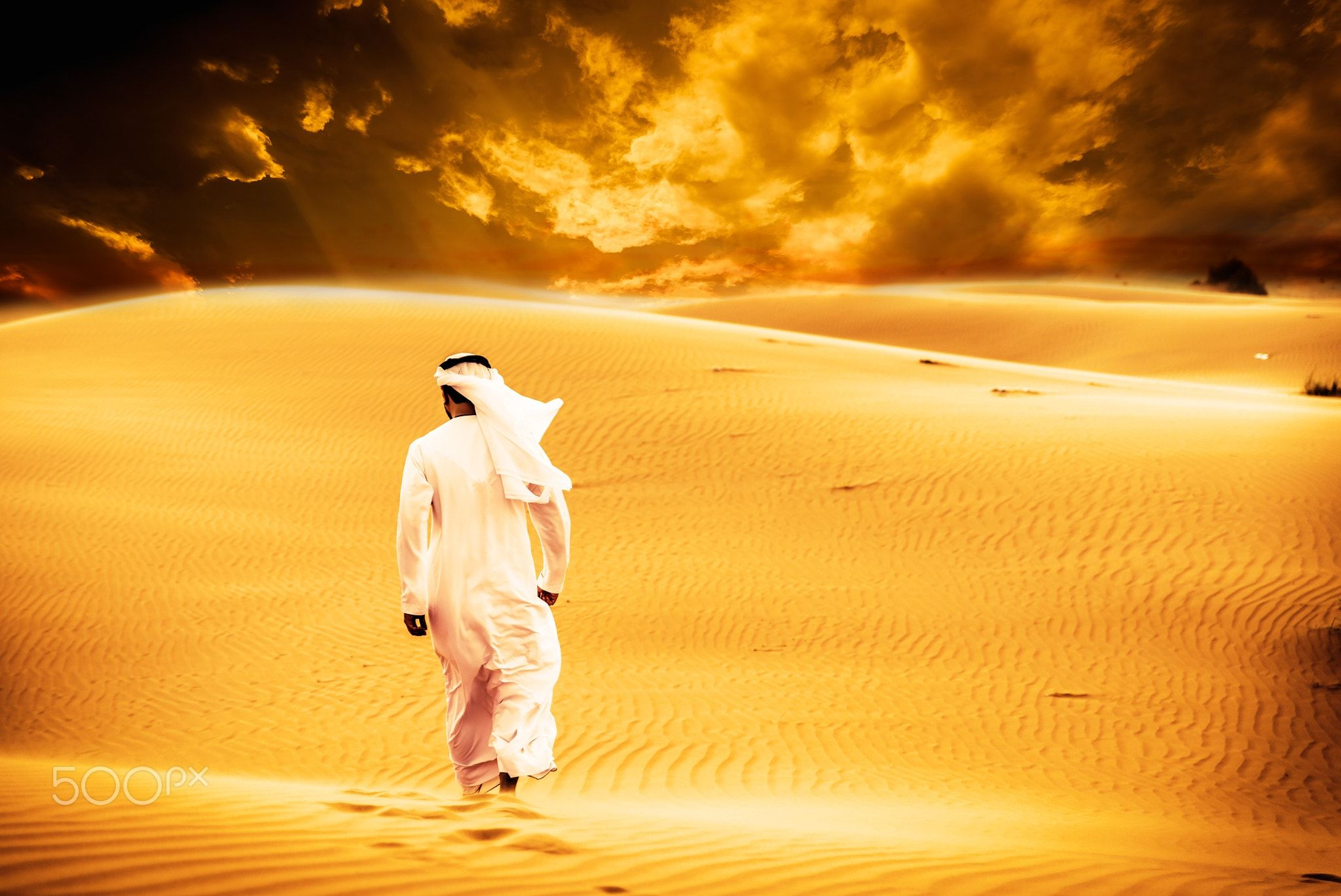Arabic Man With Traditional Emirates Clothes Walking In The Dese Arabic Man With Traditional Emirates Clothes Walking In The Desert