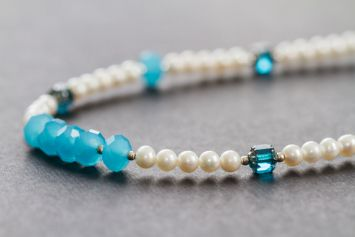 Closeup jewelry photography of a white and blue bead necklace.