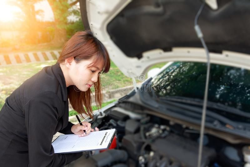Insurance Agent Writing On Car Insurance Document And Examining