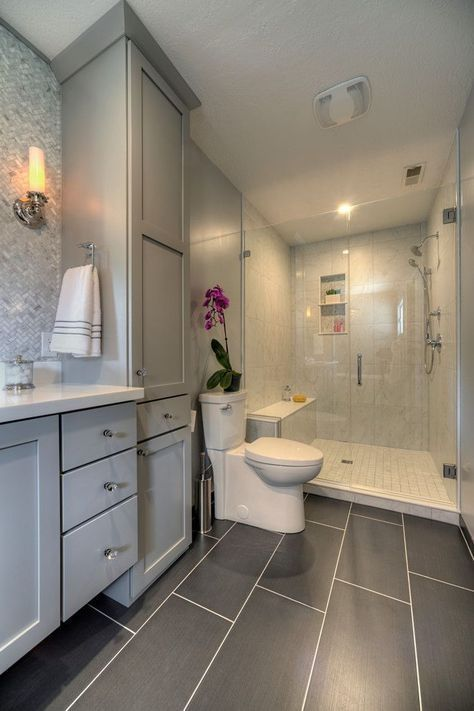 Master bathroom with glass walk in shower, large gray tiles on floor, gray cabinets & mosaic tile backsplash