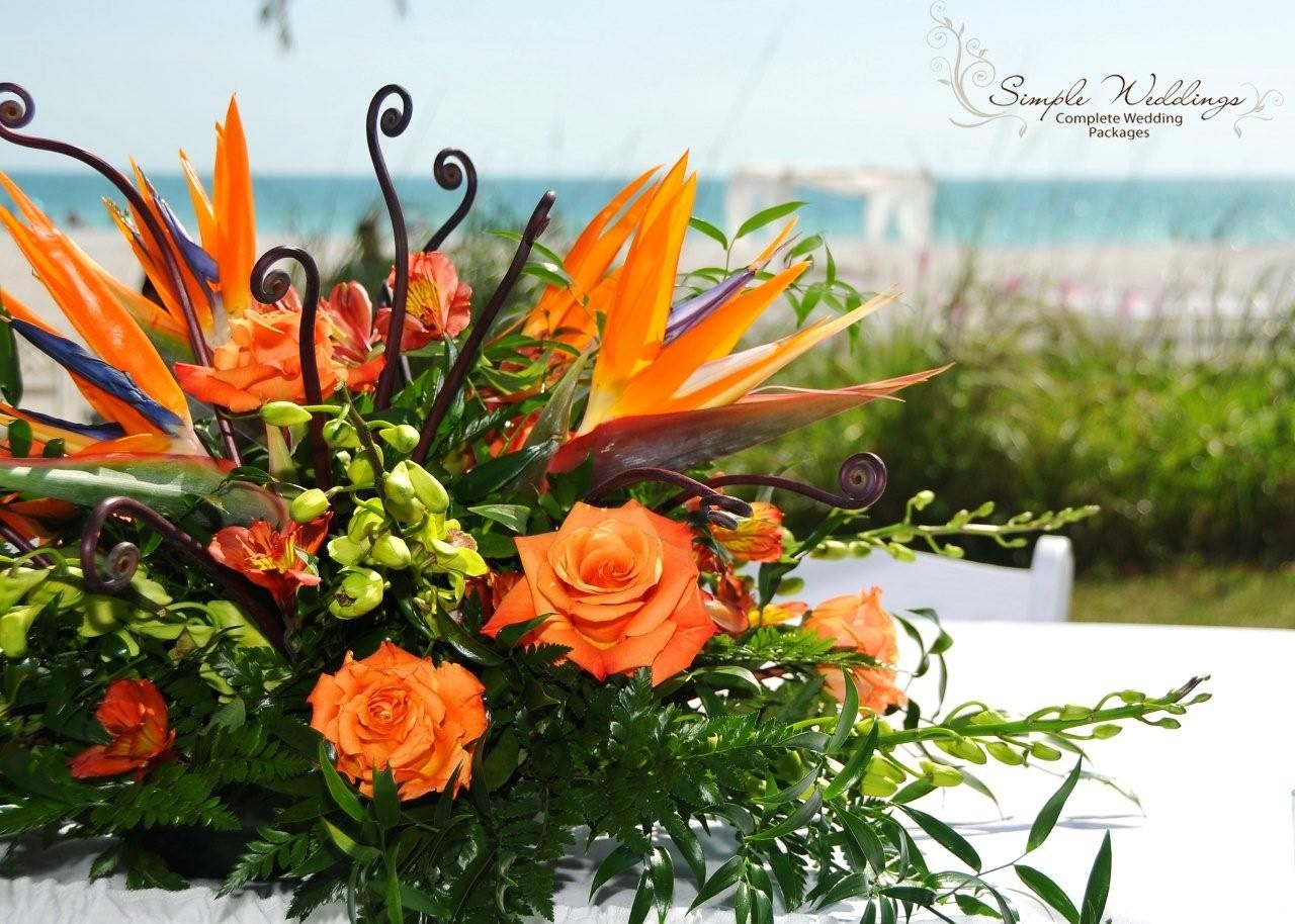 Tropical flower arrangement with orange roses and birds of