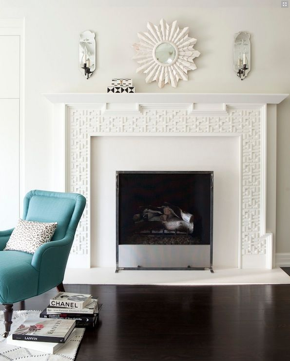 Chic Living Room Design With White Fretwork Fireplace Small Sunburst Mirror Flanked By Mirrored