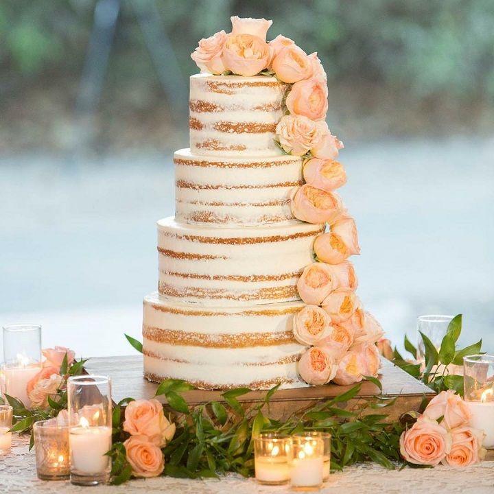 Eye-catching semi-naked wedding cake with cascading blush flowers #weddingcake #seminakedweddingcake #nakedweddingcake