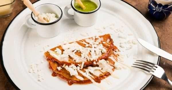 Enchiladas potosinas hecha por La Cocina De Rosina. Estas enchiladas son típicas de México se hacen con masa y chile rojo rellenas de queso.