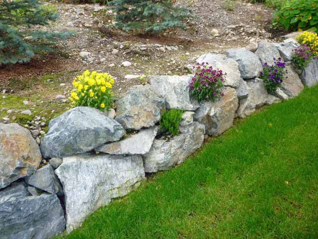 Rock Wall With Flowering Plants Landscaping With Rocks Landscaping With Boulders Rock Wall Gardens