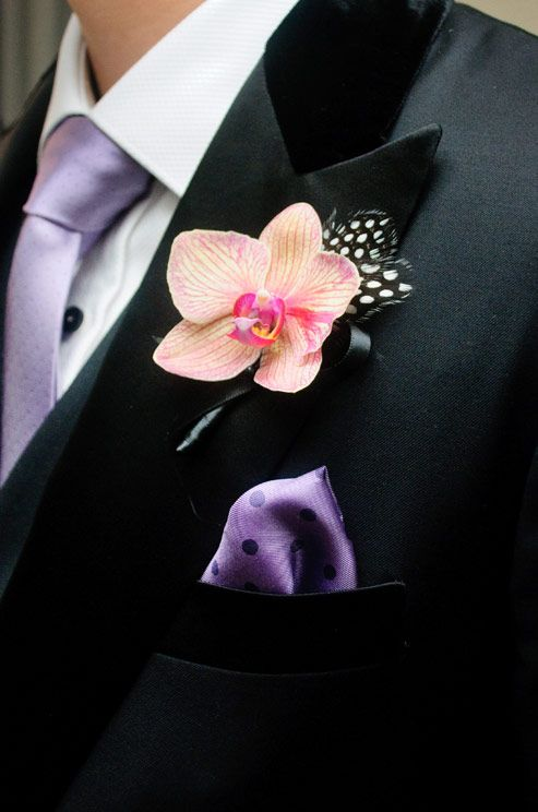 A bright pink orchid boutonniere is dressed up with