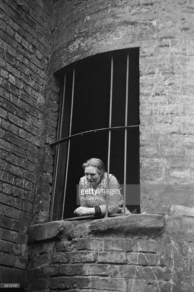 A woman looks down from a window in the Gorbals area of Glasgow The Gorbals tenements were built...