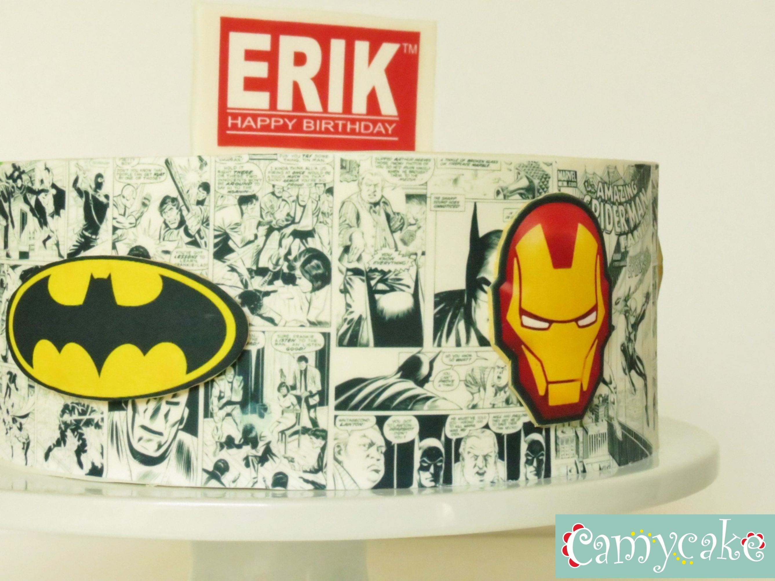 9 inch Superhero comic cake. Chocolate cake filled with madagascar vanilla ganache finished with modeling chocolate. All edible!