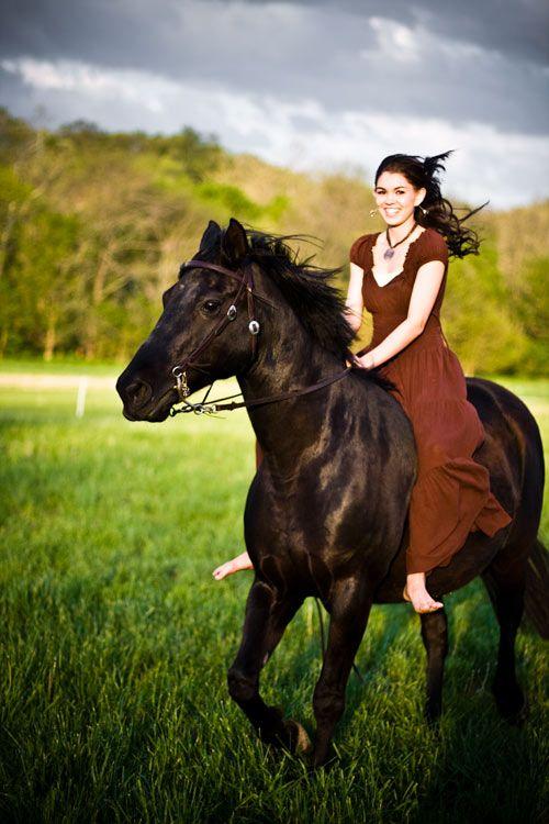 Girl in dress riding horse bareback in pasture ...