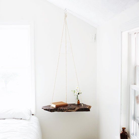 Make a hanging bedside table out of a piece of wood and some rope!