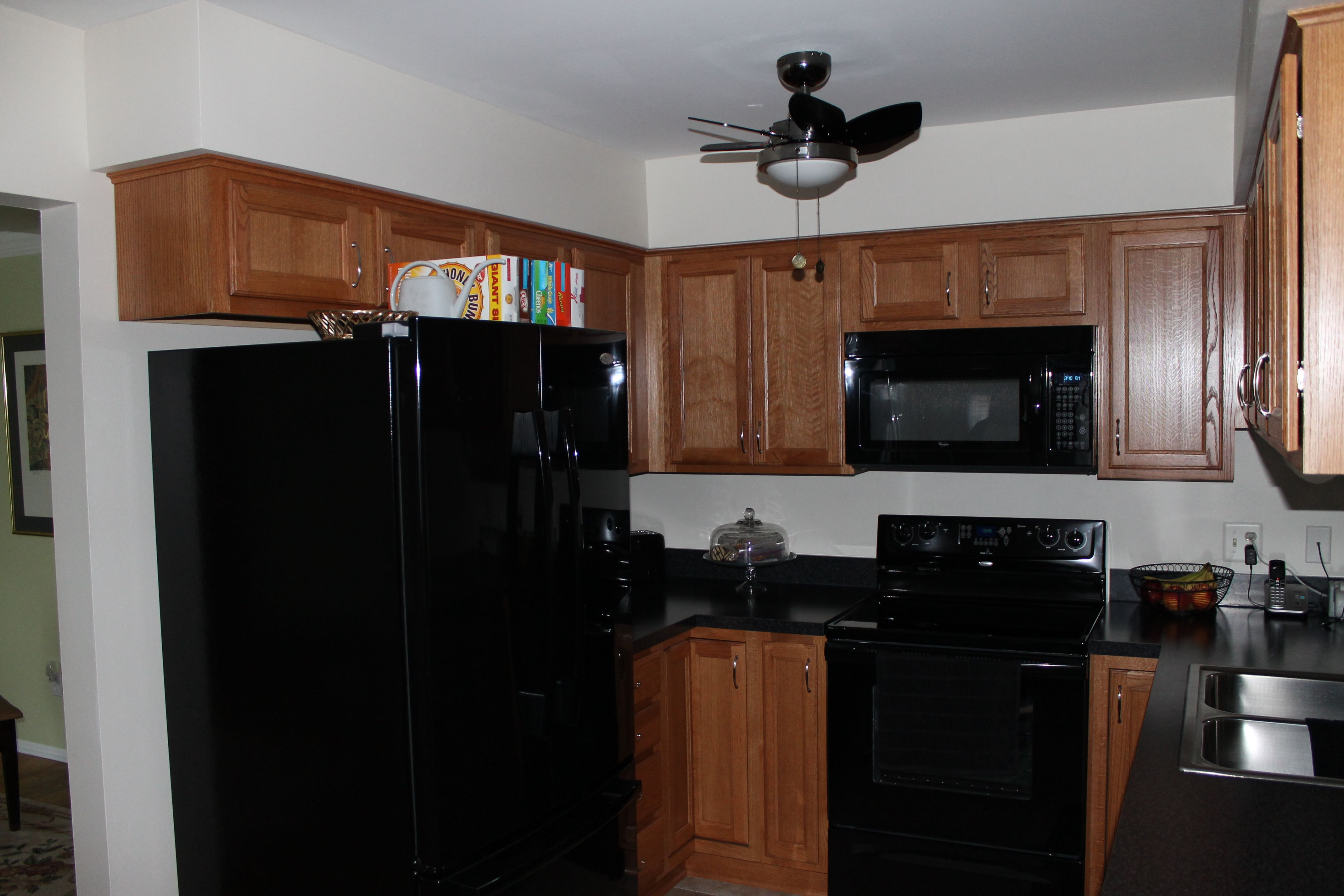 medium light shaker style cabinetry with black appliances and dark quartz countertop