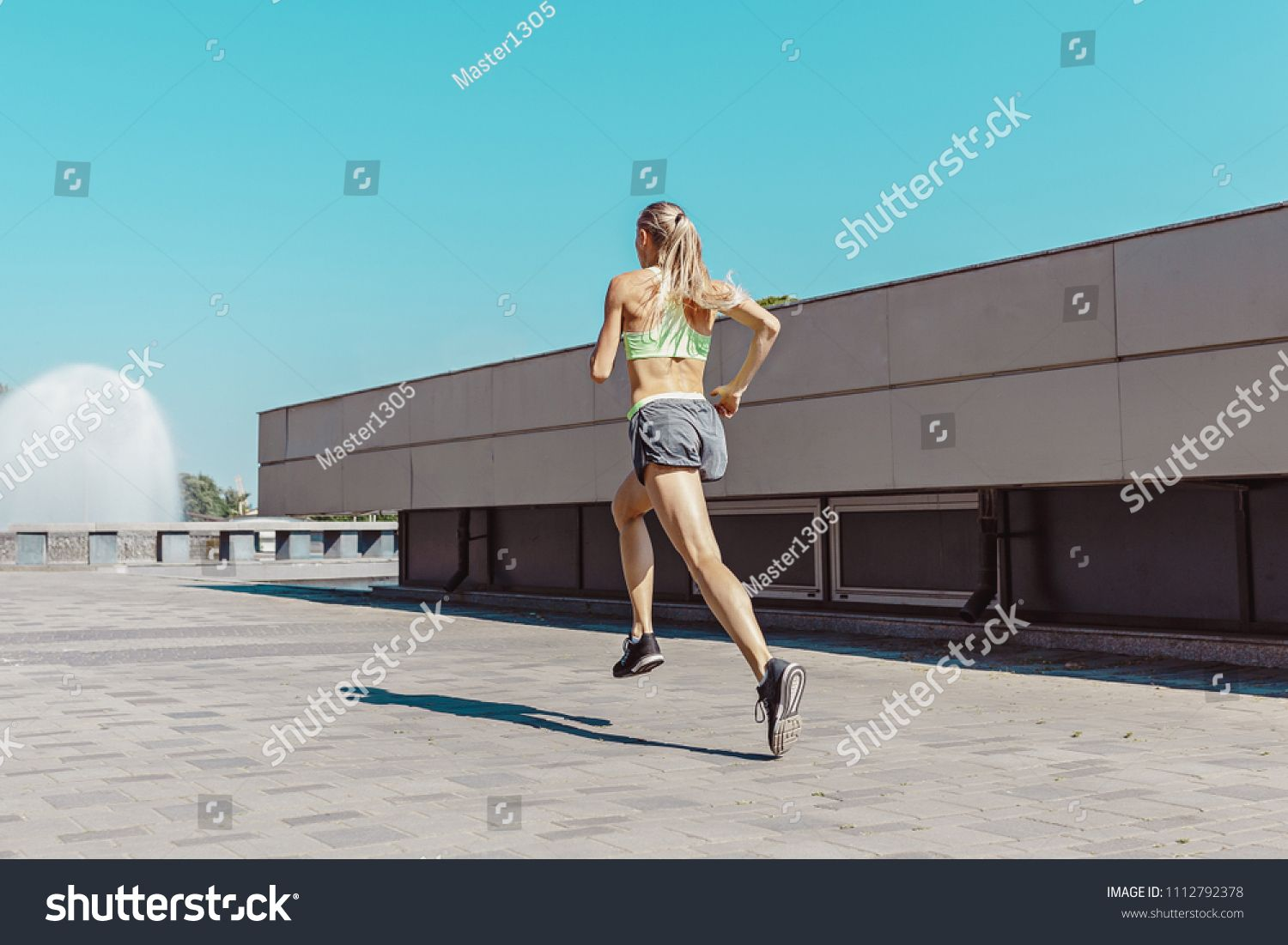 Pretty sporty woman jogging at city at morning. Fit fitness young caucasian girl running. Female sports model in summer sunny day exercising outdoor ,