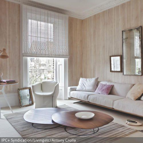 Die organisch geformten Couchtische verleihen dem Wohnzimmer ein beruhigendes und natürliches Ambiente. Dazu passend: die Motivtapete mit Holzoptik.