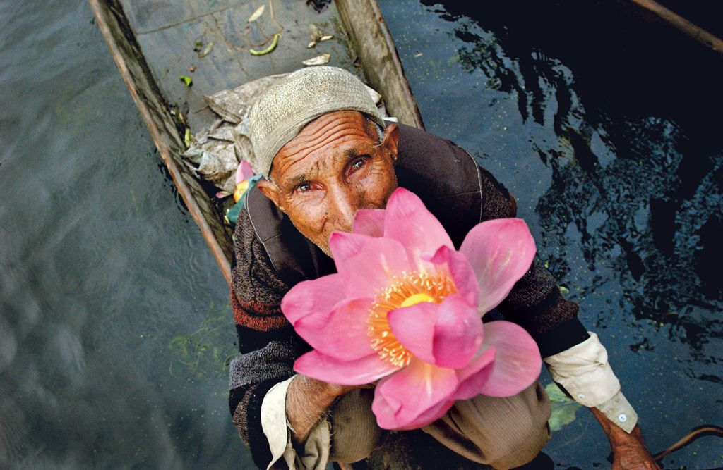 A vegetable vendor sells a lotus flower during the early