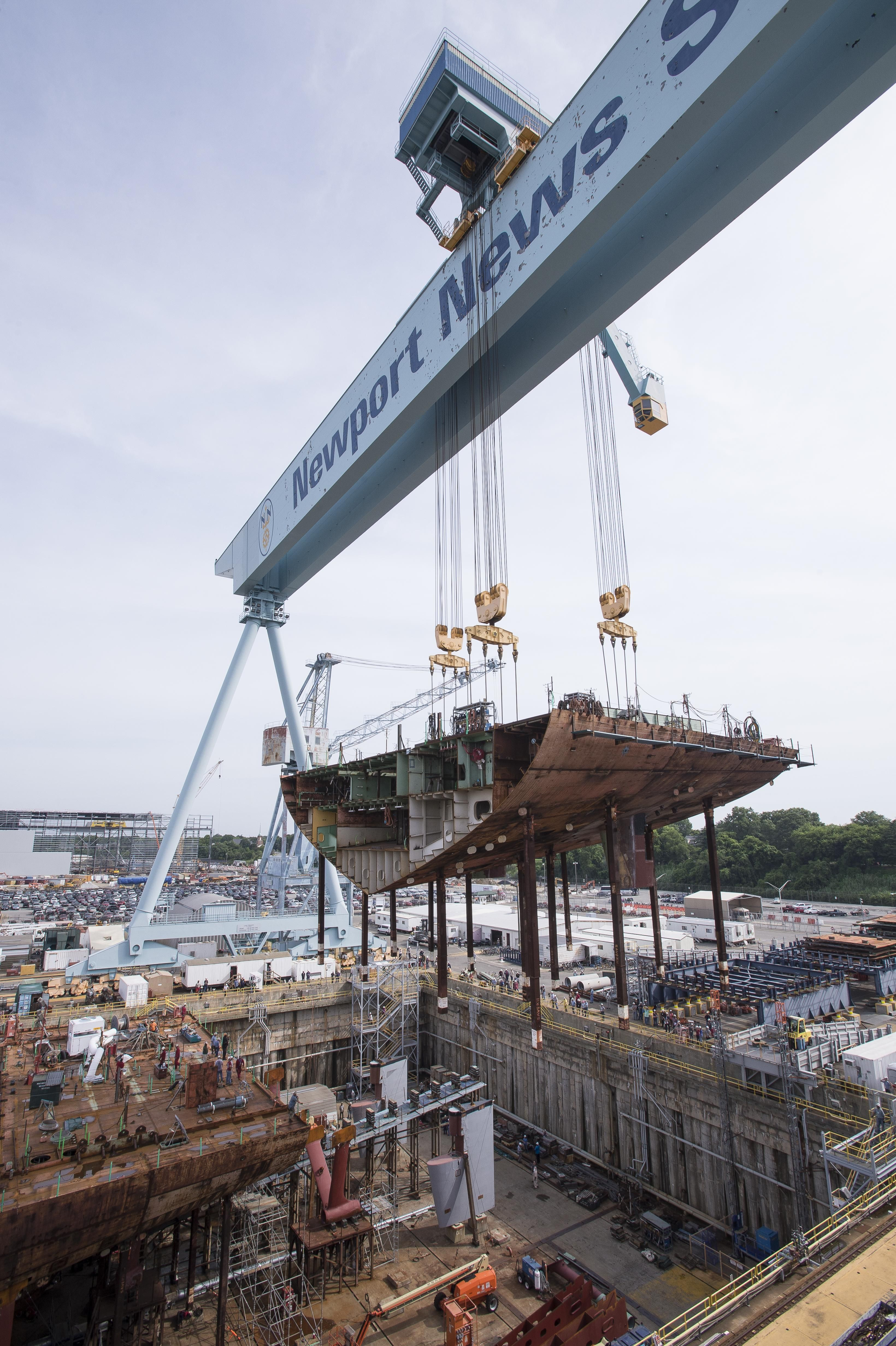 A crane moves the lower stern into place of USS John F Kennedy CVN