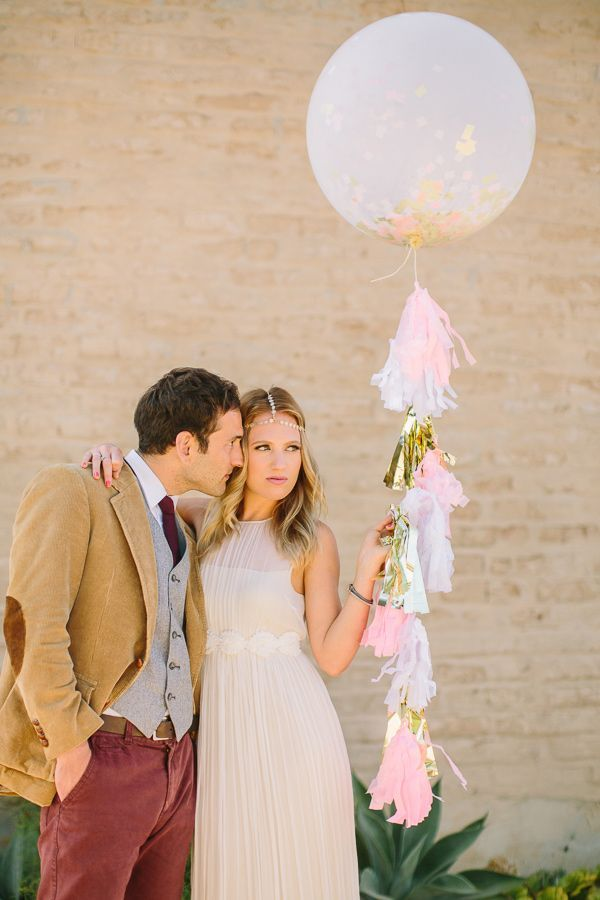 couple holding balloon filled with confetti and