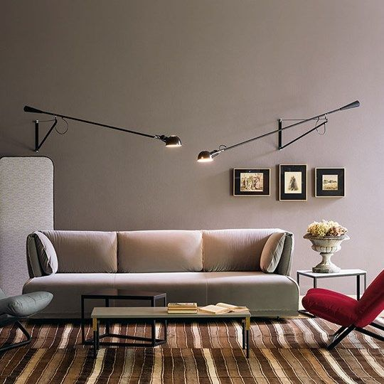 Flos 265 Lamps Establish A Welcoming Glow In This Living Room Featuring A Tan Sofa Striped Carpeting A Bright Red Chair And 265 Wall Light Wall Lights Design