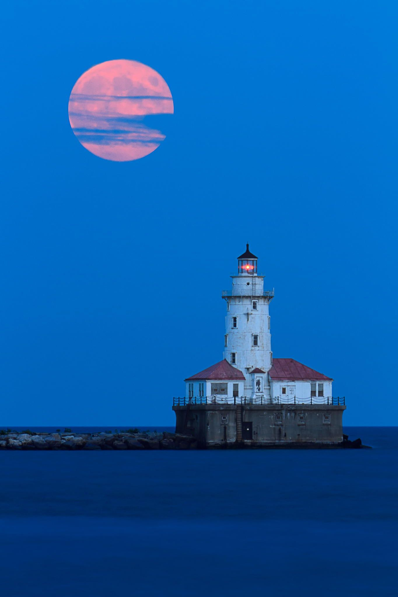 Full moon rising over the Chicago Harbor Lighthouse.