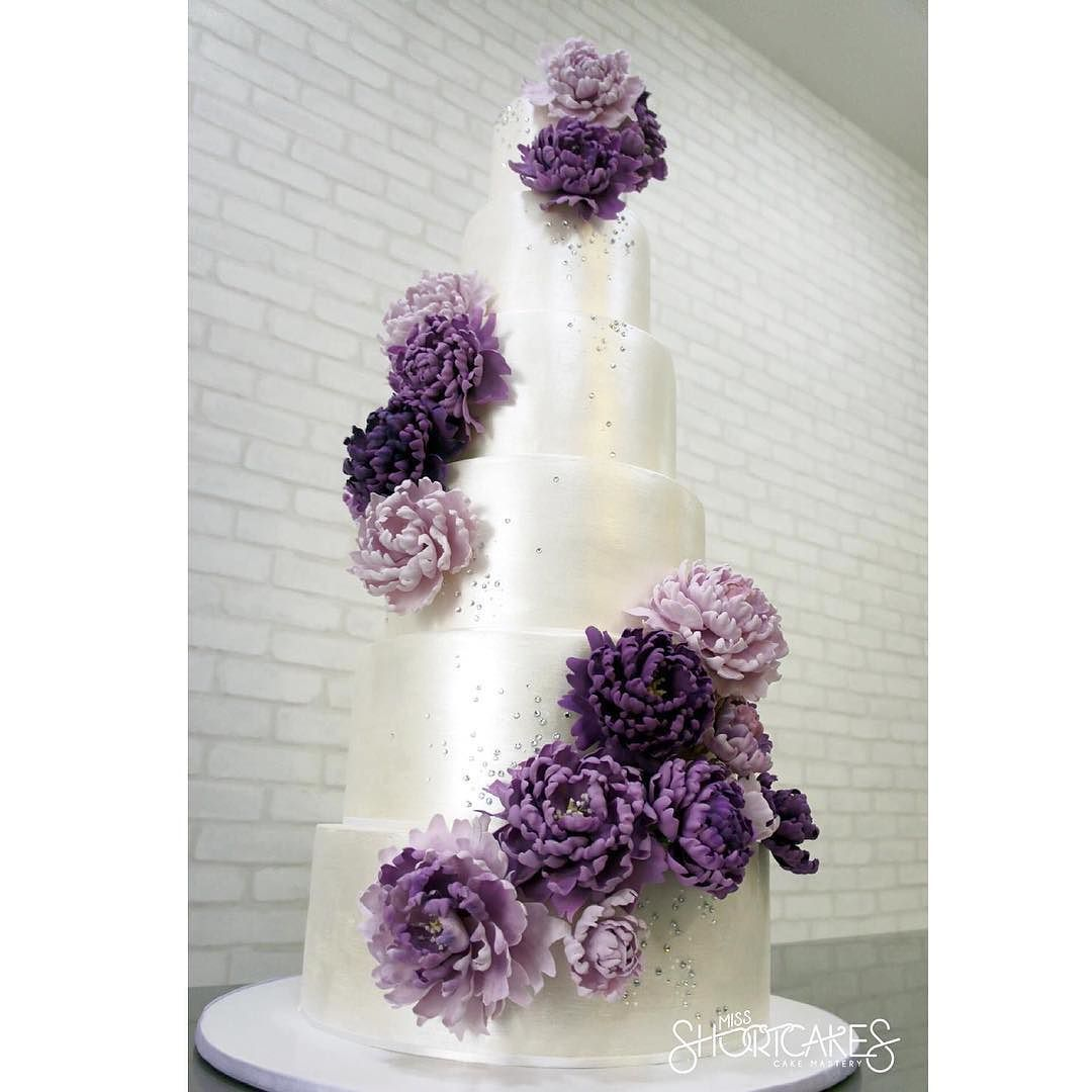 A 6 tier Swarovski crusted wedding cake adorned with oversized peonies in shades of purple. Each peony has about 23 petals that are individually wired shaped veined and curled. #missshortcakes #customcakes #weddings #weddingcakes #luxe #luxeweddings #cakespecialist #cakelife #cakeart #kualalumpur #luxeweddingcake #bling #swarovski #crystals #peonies #sugarflowers #lilac #purple #pearlwhite #luxuryweddings #inezosama by missshortcakes