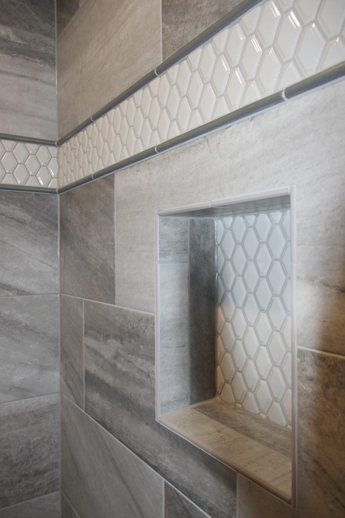 Gray Tiled Shower With White Hexagon Tiled Accent Strip And Niche