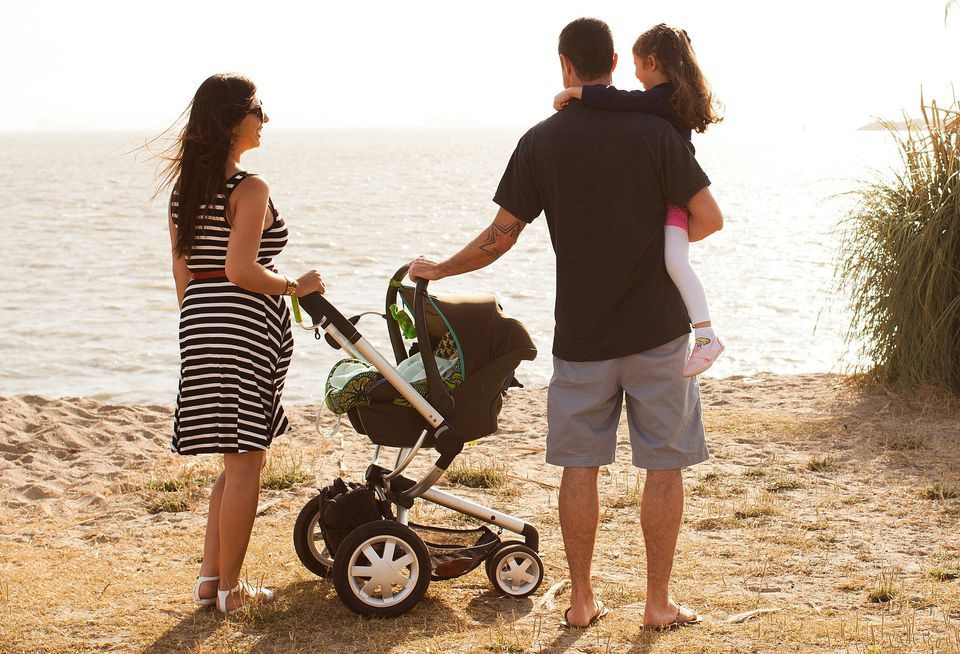 family with Travel System stroller on Beach Travel