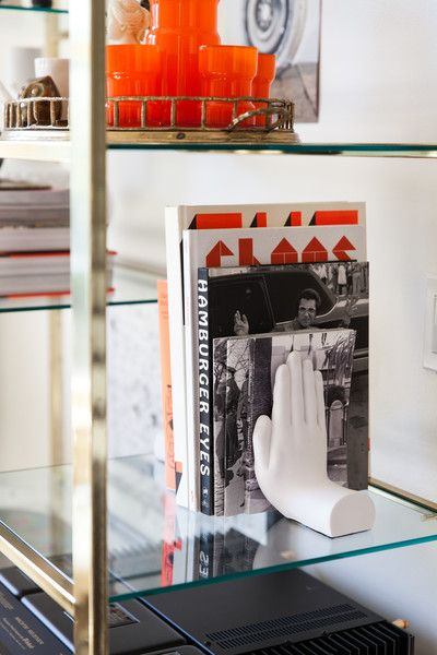 Hand-shaped bookend on glass shelving.