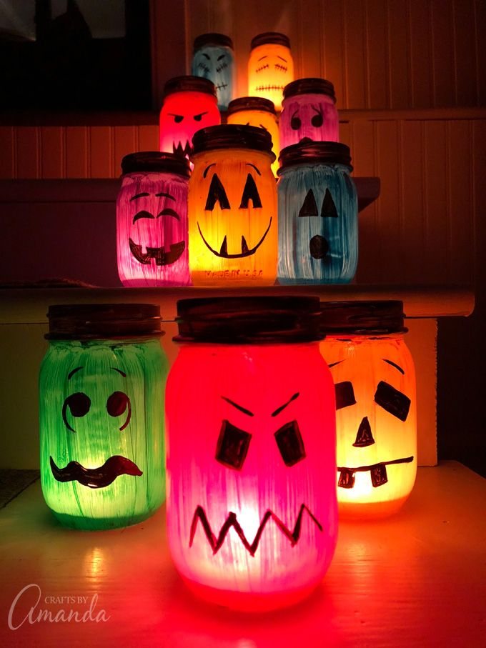 These colorful Halloween luminaries are made from painted mason jars and will light up your sidewalk or window this Halloween! #halloweenluminaries #halloweencrafts #masonjarcrafts #masonjarluminaries #paintedjarcrafts #monstercrafts #bricolagehalloweenenfant