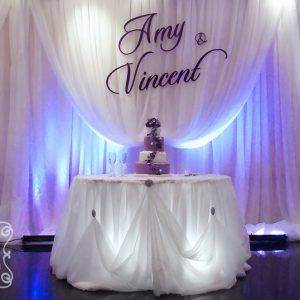 Large purple name plate on cream voile backdrop cake table a romantic cinderalla pick up style wedding reception decoration junglespirit Images