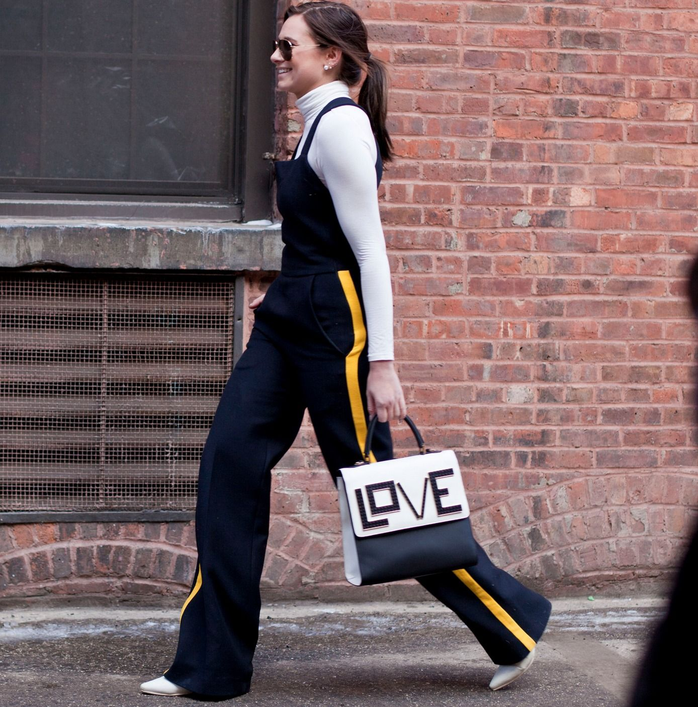 """Street Style - all of the must-see winter outfits from NYFW 2015 -  the new """"it-girl"""" Les Petits Joueurs """"LOVE"""" bag + a white turtleneck under worn with a sporty wide leg jumpsuit."""