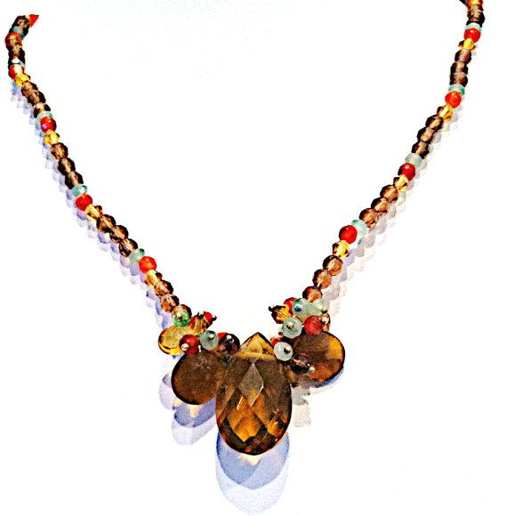 Elegant crystal necklace composed of small Swarovski crystals in amber, pale green, orange, and gold colors are strung on 16 of wire, with a 1