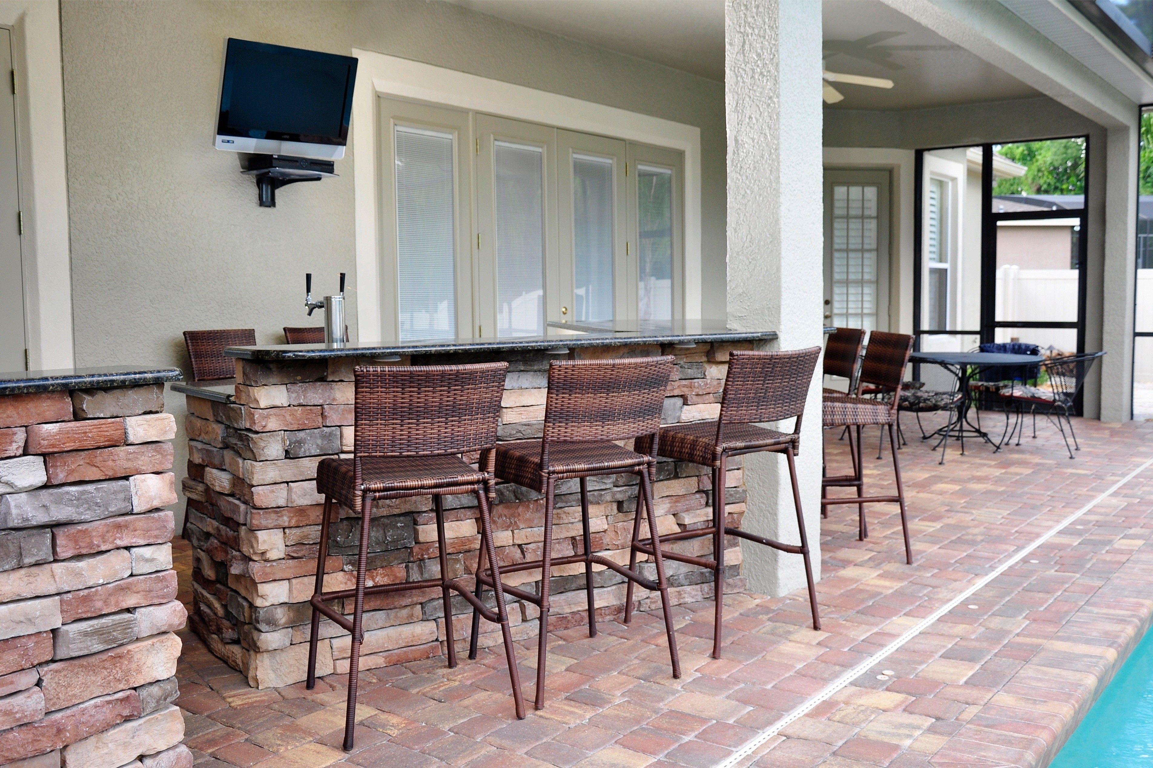Custom Stone Patio Entertainment Area, Outdoor Kitchen, Wall Mounted TV,  Barstools.