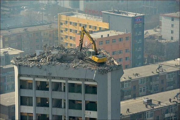 Excavador encima de un edificio