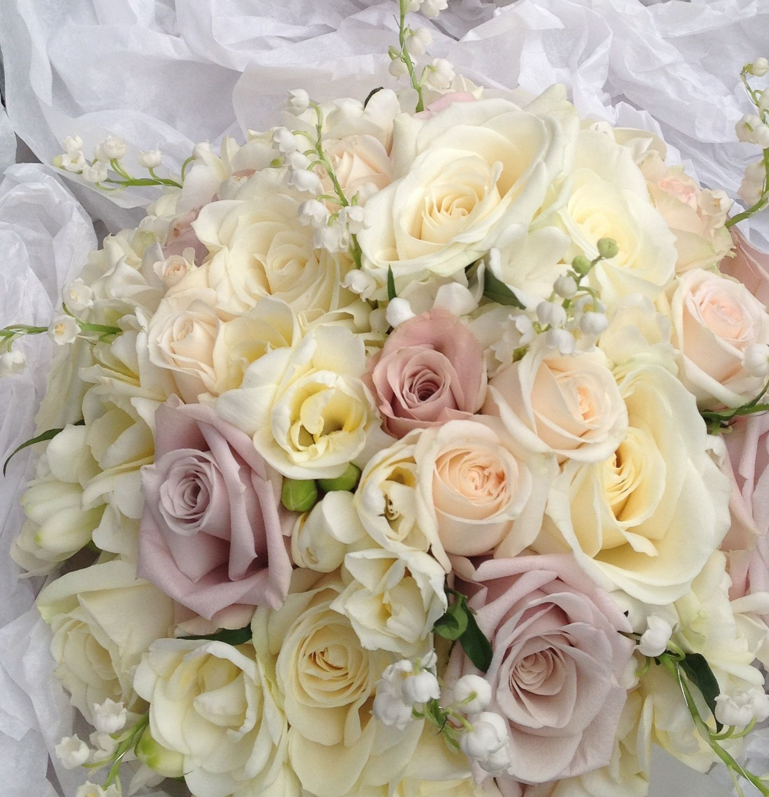 Bridal bouquet in roses, freesia, lily of the valley and