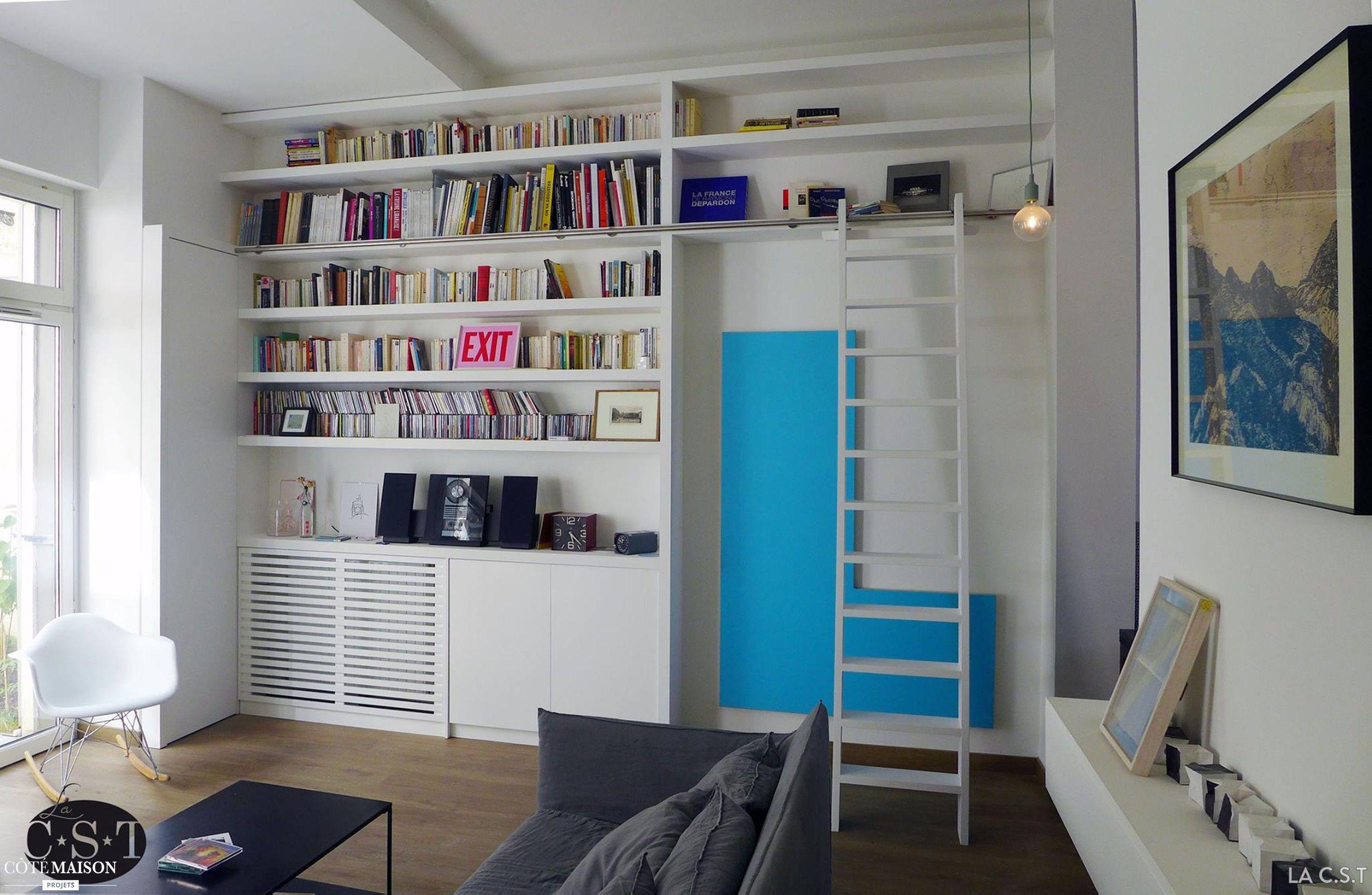 cette bibliothèque parait intégrée aux murs et remplit toutes les