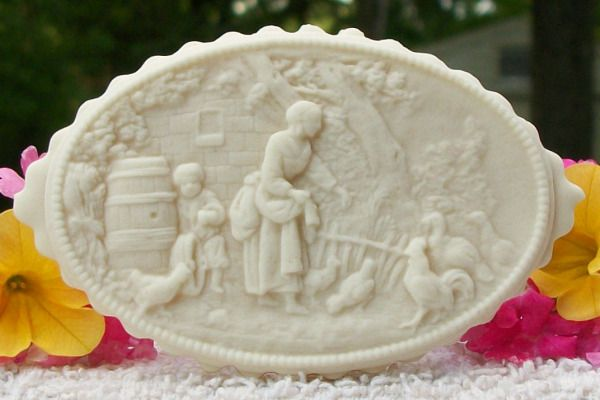 Springerle cookie: a woman feeding her chickens, ducks and turkeys while her son looks on from behind a barrel.
