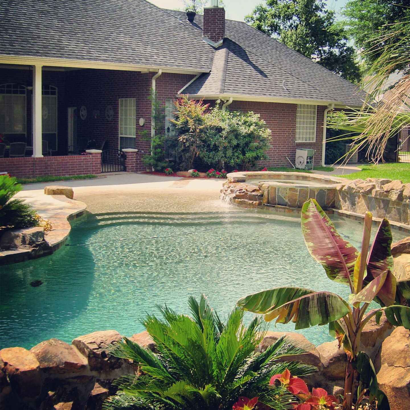 Tropical lagoon style gunite swimming pool with grotto pool cave