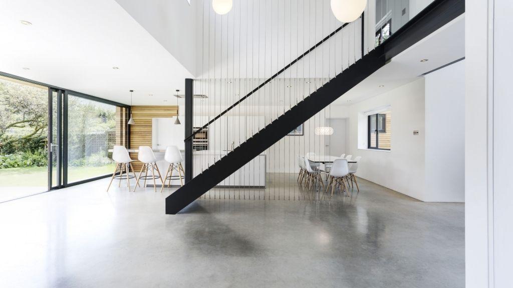 Frei im Raum stehende Stahltreppe in hellem Wohn und Esszimmer