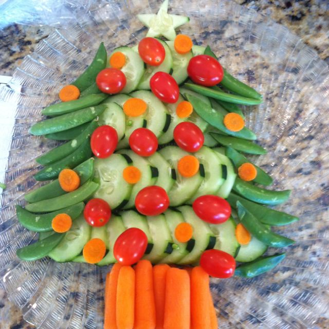 christmas tree veggie platter with sugar snap peas broccoli for the green cucumbers for the background carrots for the trunk and tomatoes for the
