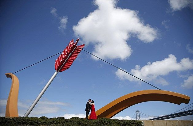 "Jose Ramirez & Flor Perez, newlyweds from Reno, Nevada, kiss in front of ""Cupid's Span,"" a sculpture by Claes Oldenburg & Coosje van Bruggen near the Bay Bridge in San Francisco, on April 4, 2014."