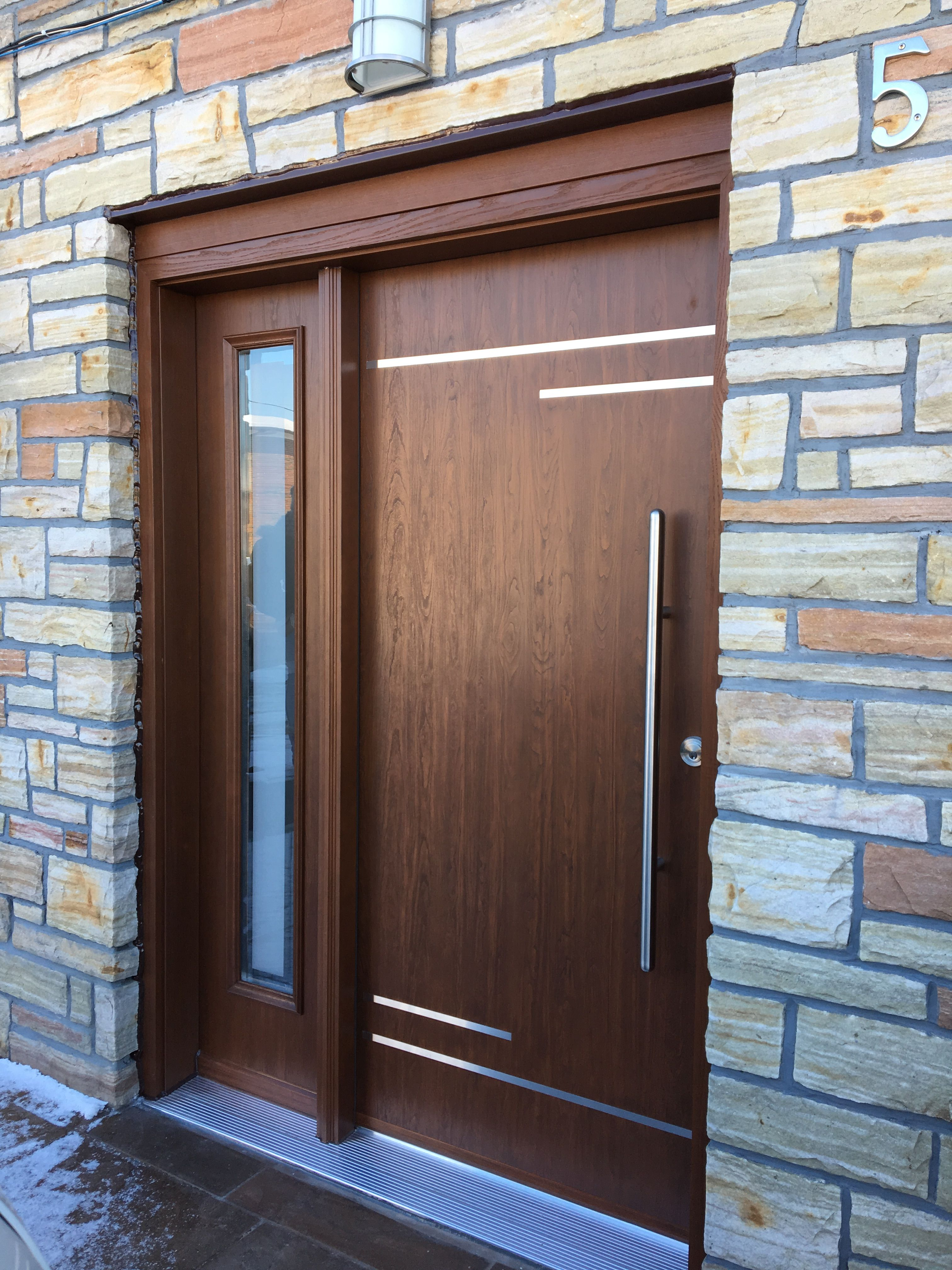Contemporary fiberglass door with stainless steel inlays and 36 pull bar stained in kv light cherry sandblast 0864 sidelite with 1 clear border