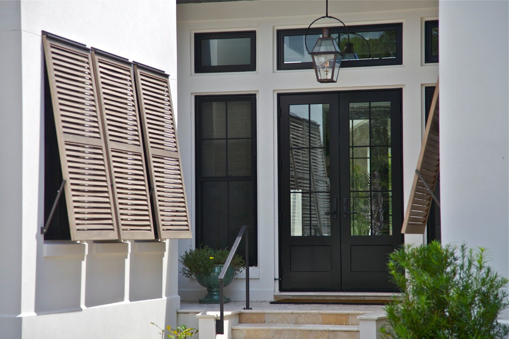 Marvin windows and aluminum clad front door with beautiful bahama shutters on this custom home - The shutter clad house ...