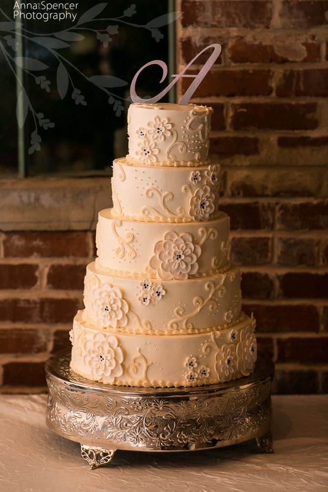 Anna and Spencer Photography , Atlanta Documentary Wedding Photography . White wedding cake with chrysanthemum and swirl icing design against a brick wall .