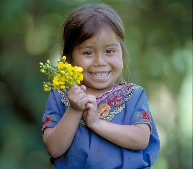 The Eyes of Children around the World    A portrait of 6 year-old Maria Molina with flowers she has picked. She is waiting with her mother for food distribution from the Save the Children Guatemala program in Chajul. released Save the Children