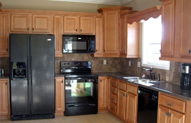 Black kitchen appliances with light wood cabinets