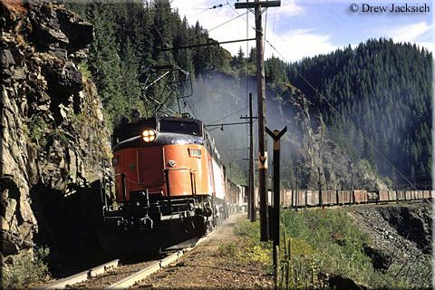 Milwaukee Road Little Joe E21 powers an eastbound manifest freight as the train climbs out of Avery, Idaho along the St. Joe River during August of 1971. Today, this right-of-way is now a highway.