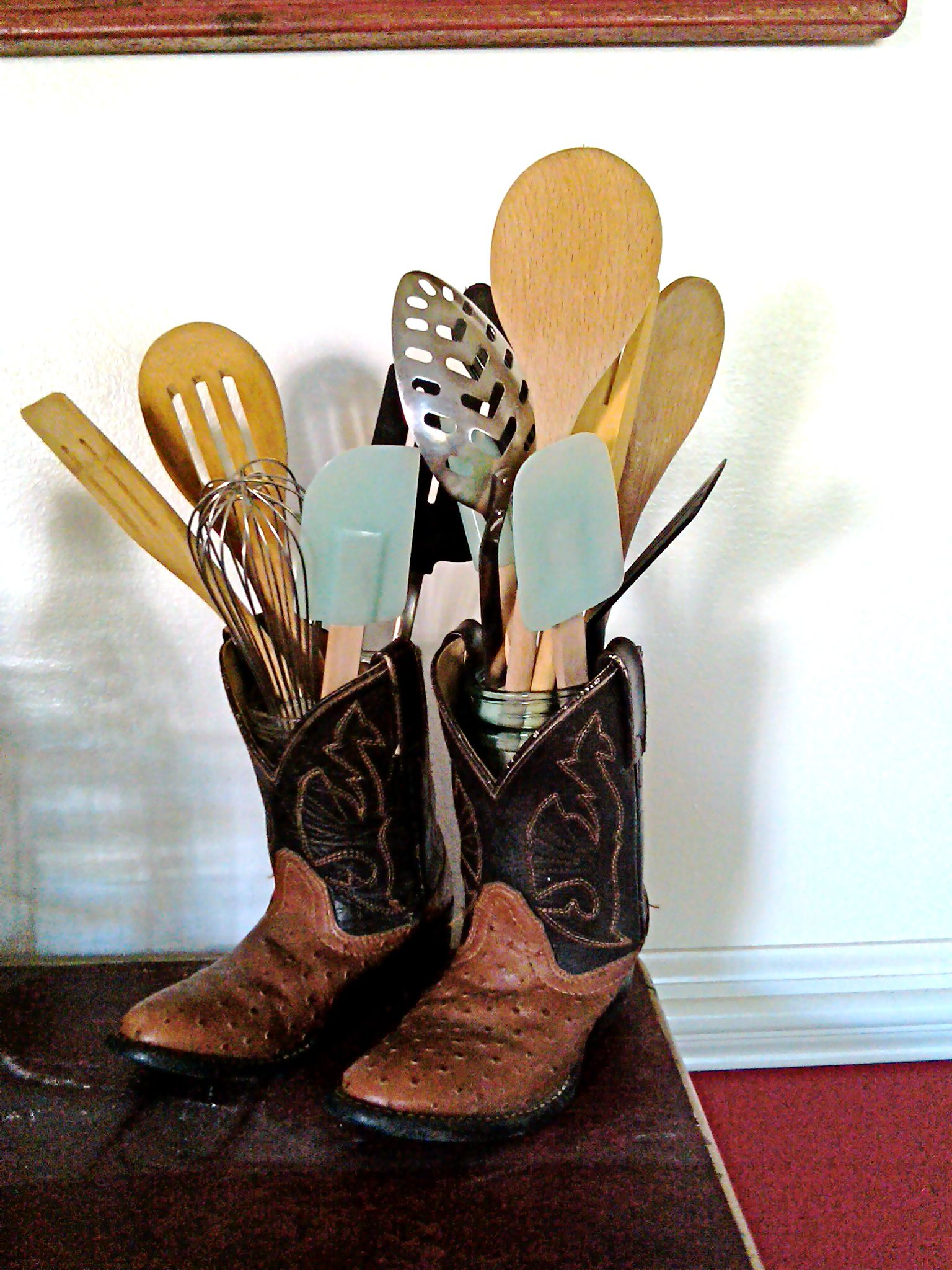 Outgrown little guy cowboy boots - place small Ball jar inside and create a new kitchen utensil holder - toss the crock!